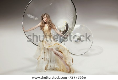 Perfect young beauty sitting on martini glass