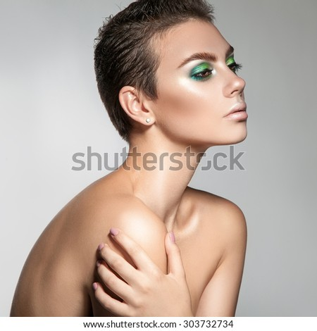 Perfect young woman with beautiful makeup and short hair looking away. square photo. grey background - stock photo