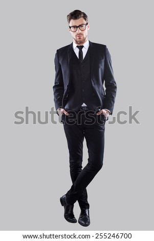 Perfection in every detail. Full length of confident young man in formalwear and eyeglasses holding hands in pockets and looking at camera while standing against grey background - stock photo