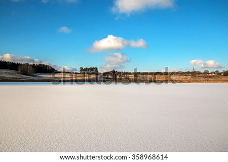 Perfectly flat frozen lake covered with fresh white snow for ice skating - stock photo