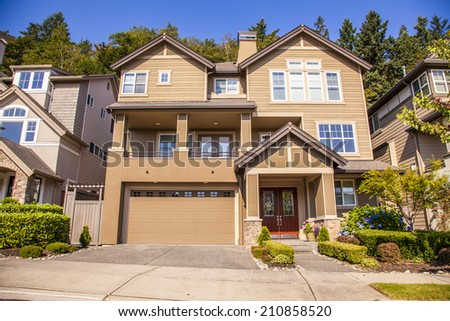 perfectly manicured suburban house on a beautiful sunny day  - stock photo