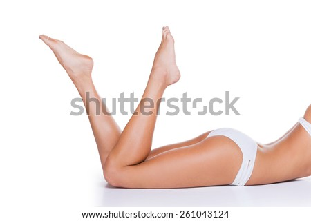Perfectly smooth skin. Close-up of beautiful woman in white panties lying against white background and keeping her feet up - stock photo