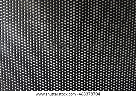 Perforated back of a black metallic chair.