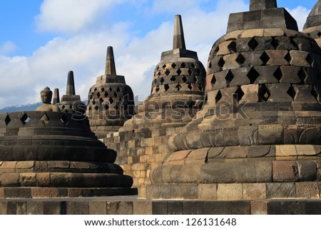 Perforated stupas and Buddha statue on the top of giant Buddhist monument Borobudur in Java, Indonesia.