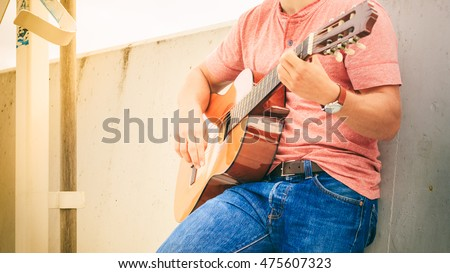 Performance and show on fresh air. Part body of young fashionable man playing classic guitar outdoor. Summer time.