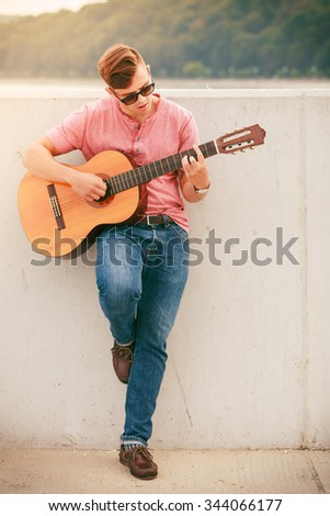 Performance and show time. Young fashionable man wearing sunglasses playing classic guitar outdoor.
