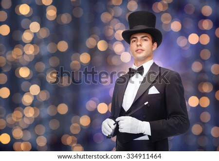 performance, circus, people and show concept - magician in top hat with magic wand over nigh lights background - stock photo
