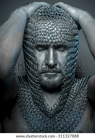 Performance, medieval executioner mesh iron rings on the head - stock photo