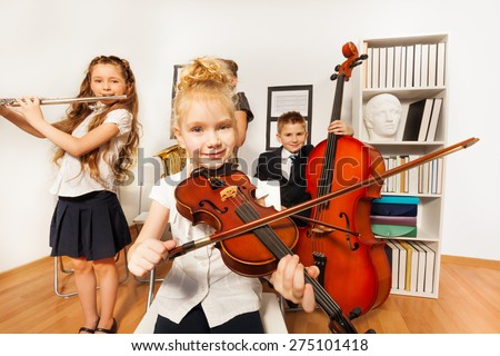 Performance of kids who play musical instruments - stock photo