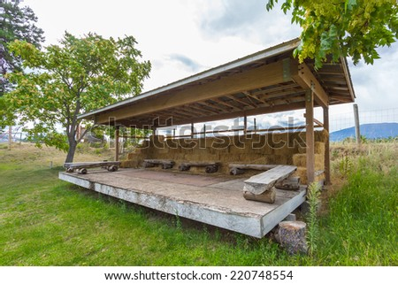 Performance stage made of wood with log seats and hay - stock photo