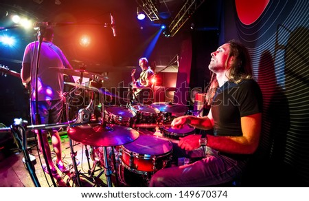 Performances of the musicians, the drummer in the foreground, rock music concert - stock photo