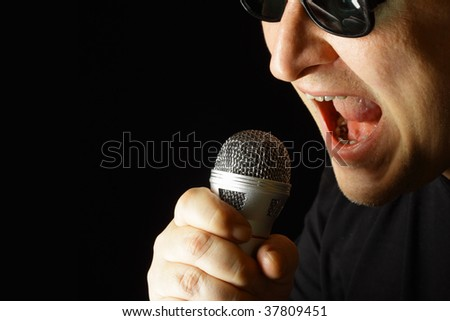 Performer with microphone over black background - stock photo