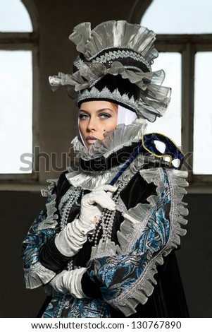 Performers in costume for a Venetian carnival against window - stock photo