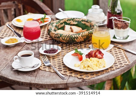 Perfrect healthy breakfast on patio in summer day. Fried eggs, cappuccino, fruits and muesli. Yummy and delicious - stock photo