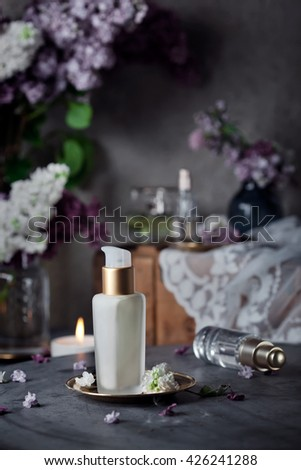 Perfume and face/body creams with fresh lilac flowers, vintage styled, dark style photo. Toned photo. - stock photo