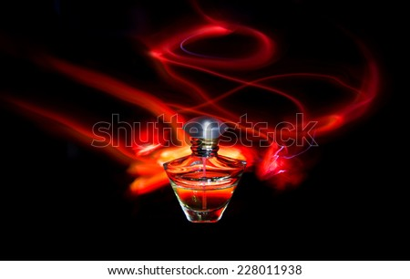 Perfume bottle and red light painting on the black background - stock photo