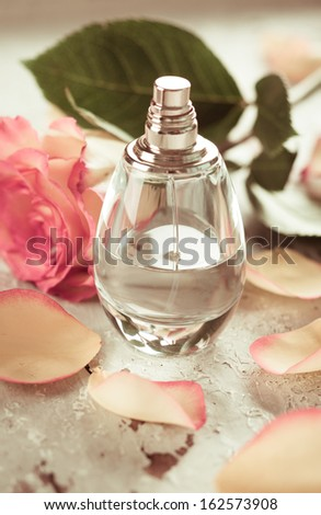 perfume bottle and rose on the old desk  in vintage style - stock photo