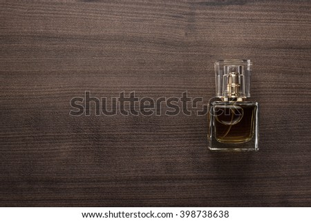 perfume bottle on the wooden background - stock photo