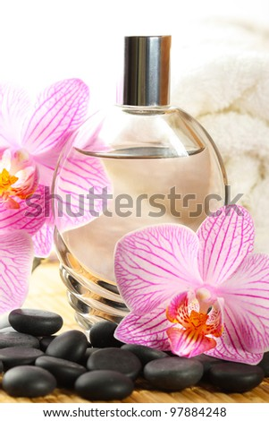 Perfume bottle, orchid flower and white towel. - stock photo