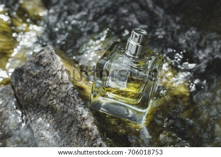 Perfume bottle over water background
