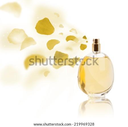 Perfume bottle spraying colorful rose petals - stock photo