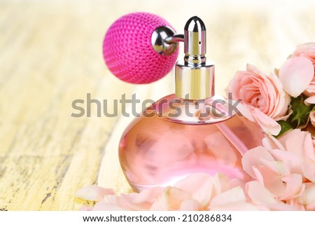 Perfume bottle with petals on table close-up - stock photo