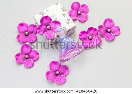 perfume bottle with some purple and pink decorations on white background
