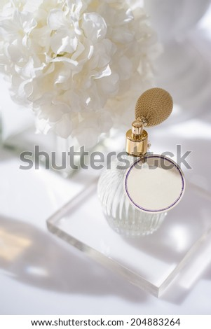 perfume bottle with white flower - stock photo
