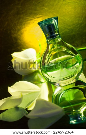 Perfume bottle  with white rose isolated on green background - stock photo