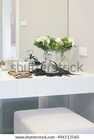 Perfume, sunglasses and flower's jar on modern style dressing table