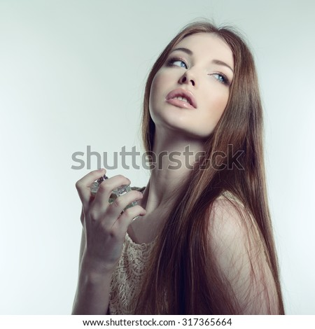 Perfume. Young pretty woman smelling aroma with pleasure, image toned. - stock photo