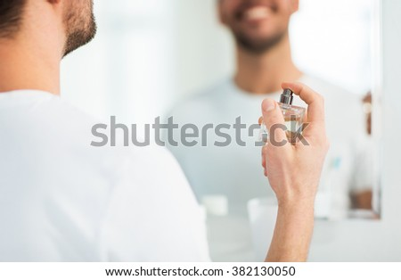 perfumery, beauty and people concept - close up of happy smiling young man with perfume looking to mirror using scent at bathroom - stock photo