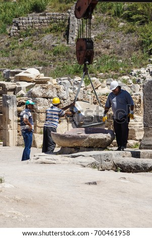 PERGE, TURKEY - JUN 2, 2014 - Workers use modern equipment to restore ancient columns in  Perge,  Turkey