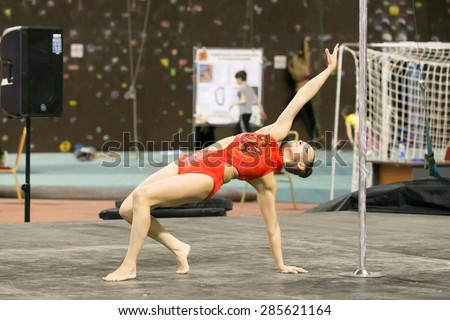 Perm, Russia - April 25, 2015. Championship Perm region at pole sport and dance. girl in an orange swimsuit makes the item bridge on one hand  - stock photo
