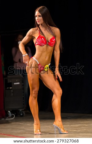 Perm, Russia - April 19, 2015.Cup Perm Krai  on bodybuilding and fitness bikini. Brunette with long hair stands sideways to the judges - stock photo