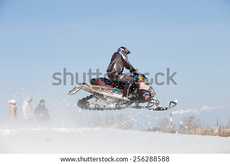 Perm, Russia - February 23, 2015. Championship on Cross Country Snowmobile. Man jumping on snowmobile on background blue sky - stock photo