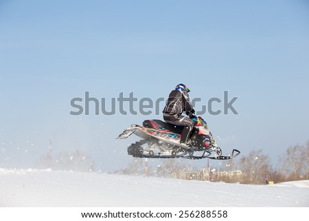 Perm, Russia - February 23, 2015. Championship on Cross Country Snowmobile.  Man jumping on black snowmobile on background blue sky - stock photo