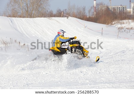Perm, Russia - February 23, 2015. Championship on Cross Country Snowmobile. racer on yellow  Snowmobile  enters  sharp turn