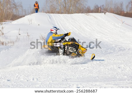 Perm, Russia - February 23, 2015. Championship on Cross Country Snowmobile. Racer on yellow snowmobile raises clouds of snow