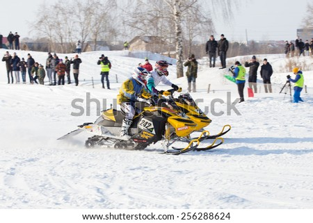 Perm, Russia - February 23, 2015. Championship on Cross Country Snowmobile. Two snowmobile riders and spectators at competitions