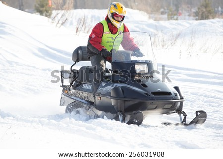 Perm, Russia - February 23, 2015. Championship on Cross Country Snowmobiles.  Racer in protection on black snowmobile day