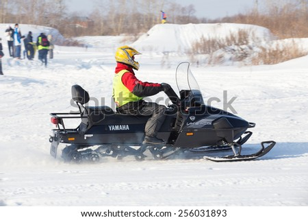 Perm, Russia - February 23, 2015. Championship on Cross Country Snowmobiles. Racer in protection on black snowmobile