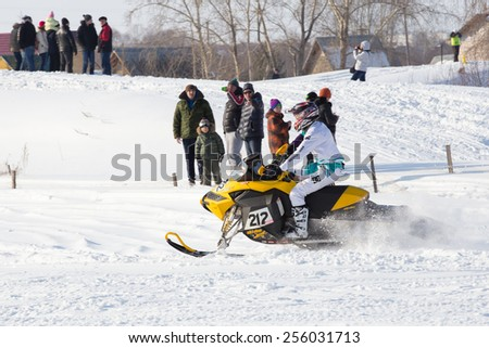 Perm, Russia - February 23, 2015. Championship on Cross Country Snowmobiles. Snowmobile rider on yellow and viewers