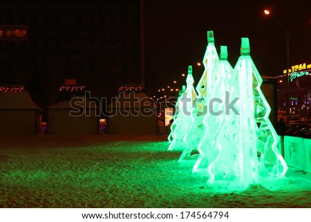 PERM, RUSSIA - JAN 11, 2014: Illuminated green ice Christmas trees in Ice town at evening. Construction of Ice town of Perm was spent 590 thousand dollars. - stock photo