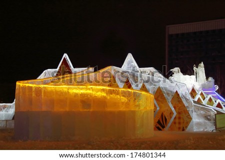 PERM, RUSSIA - JAN 11, 2014: Illuminated orange ice slide in Ice town at evening. Construction of Ice town of Perm was spent 590 thousand dollars. - stock photo