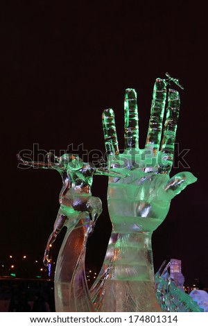 PERM, RUSSIA - JAN 11, 2014: Illuminated sculpture Hand and dancing woman in Ice town at evening. Construction of Ice town of Perm was spent 590 thousand dollars. - stock photo