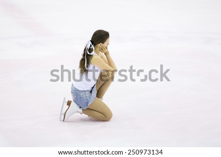 Perm, Russia - January 31, 2015. Figure skating competitions among fans. Girl in a denim skirt and white shirt kneel on ice skates