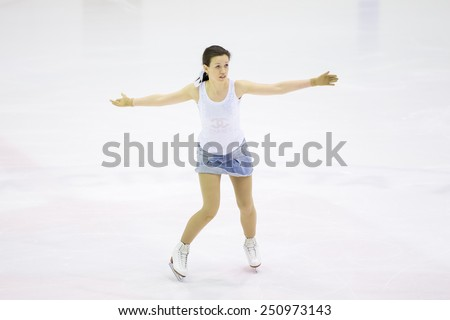 Perm, Russia - January 31, 2015. Figure skating competitions among fans. Girl in a denim skirt and white shirt dancing on ice skates on  competitions