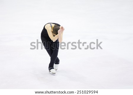 Perm, Russia - January 31, 2015. Figure skating competitions among fans.  Young woman in black suit dancing on skating in rink