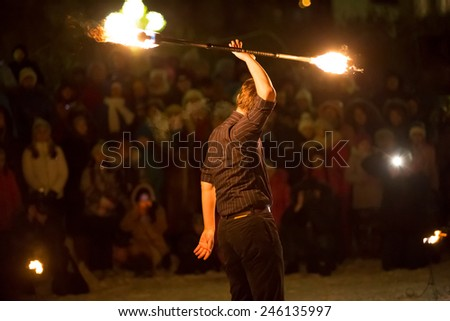 Perm, Russia - January 17, 2015. man in black suit holding fire stick over his head